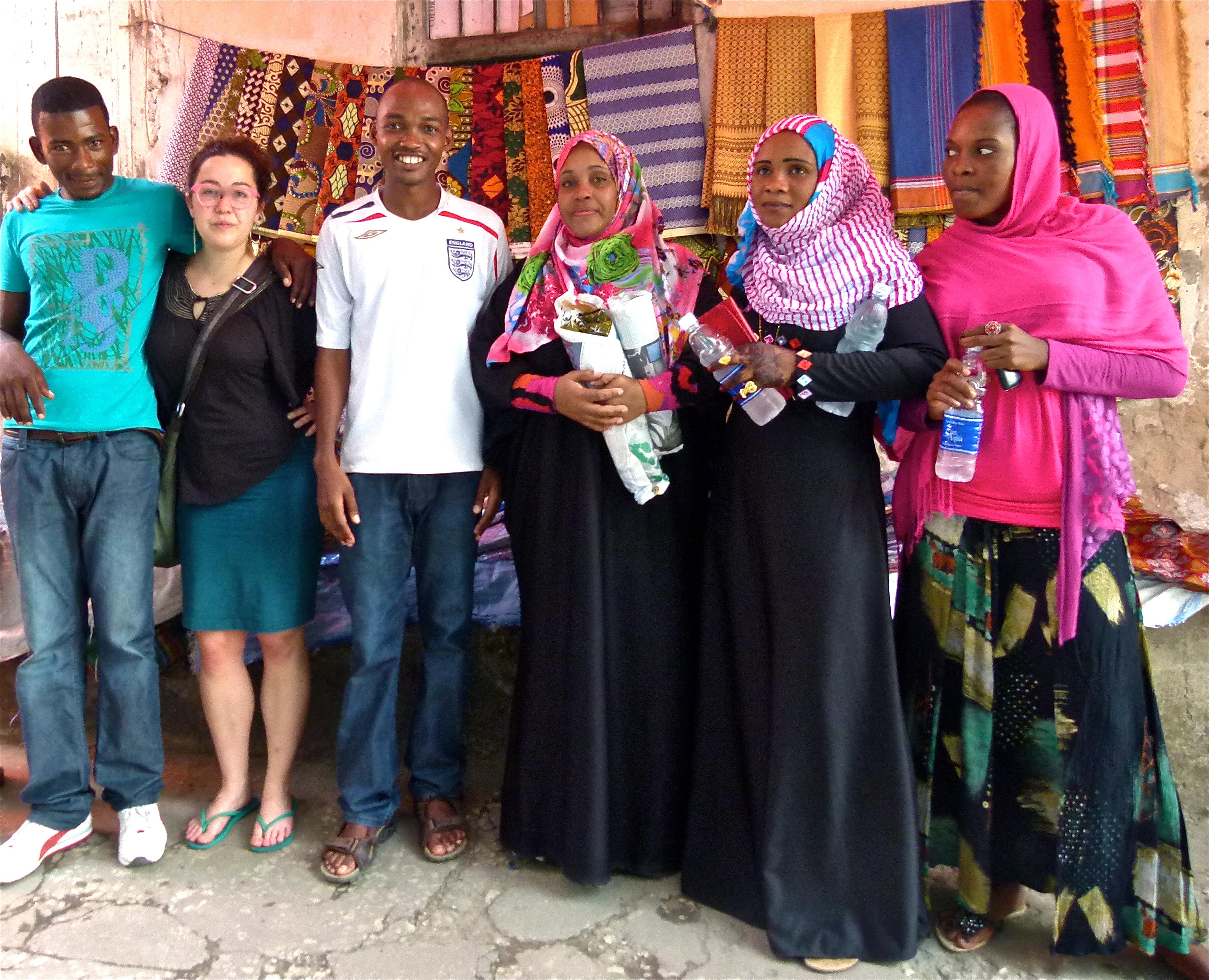 Islamisch gekleidete Sansibaris vor einem Stand mit bunten afrikanischen Stoffen