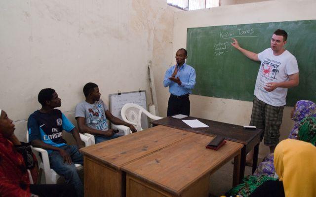 Jos erklärt Wörter, die er an eine Tafel geschrieben hat, einige Sansibari Studenten hören zu