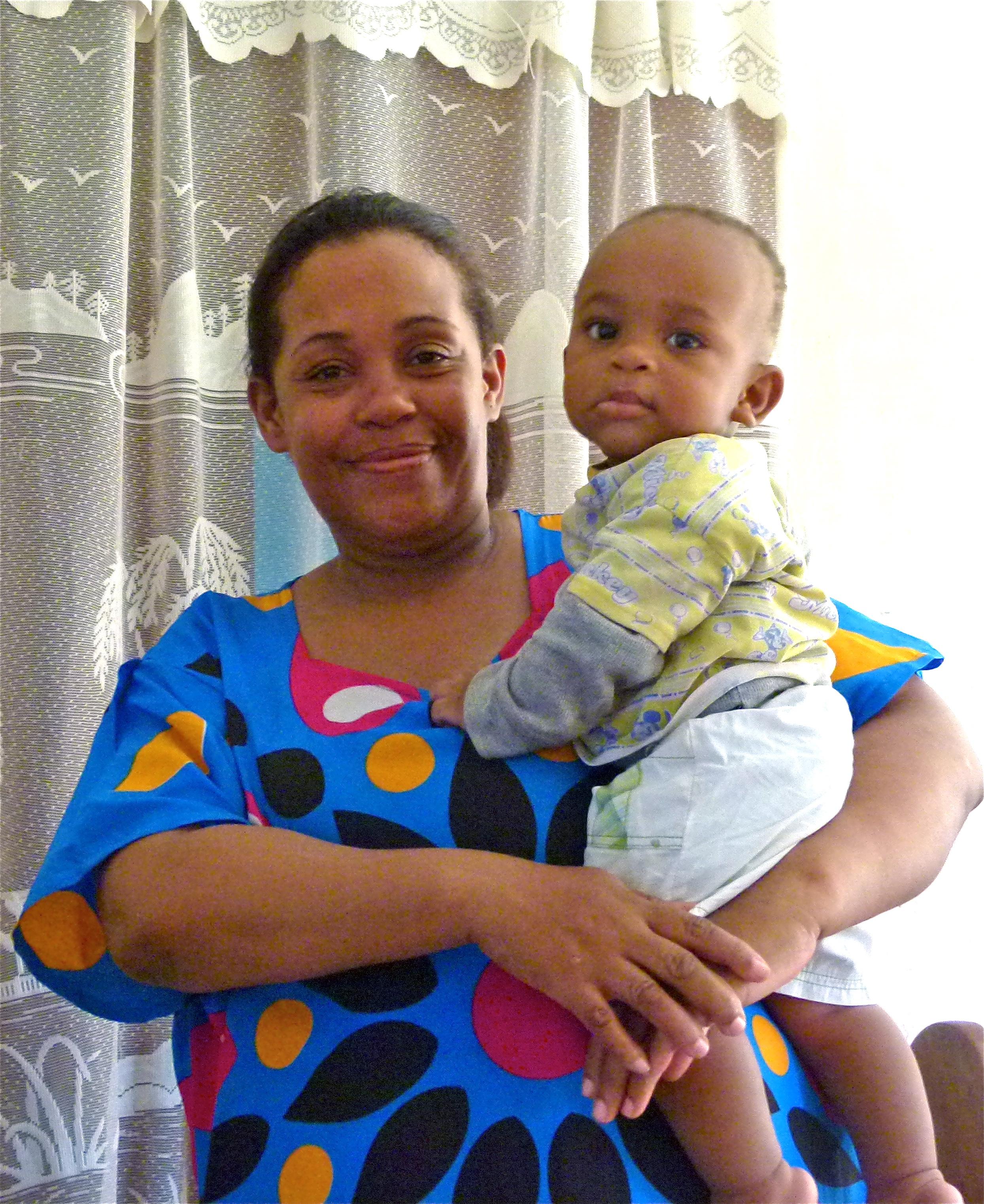Eine stolze Sansibari aus der Gehörlosen-Gemeinschaft trägt ihren kleinen Sohn am Arm