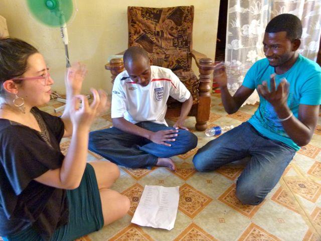 Drei Menschen sitzen sich am Boden gegenüber und üben Gebärden