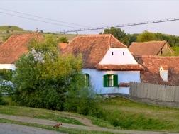 Ein schön renoviertes Bauernhaus mit blauen Mauern und einem roten Dach