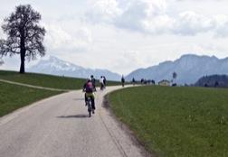 Radfahrer auf einem Weg, dahinter Berge