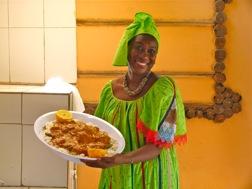 Eine Gambierin in grünem Kleid mit passendem Kopftuch präsentiert einen Teller mit Domoda