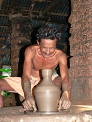 Ein Mann mit entblößtem Oberkörper hockt vor einer Töpferscheibe, auf der eine Vase entsteht
