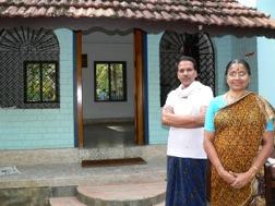 Eine Frau in Sari und ein Mann im weißen Hemd stehen vor ihrem Haus