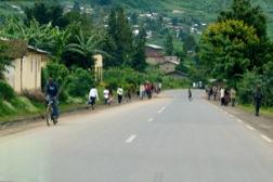 Eine Landstraße führt durch grüne Hügel. Auf beiden Seiten der Straße sieht man Menschen.