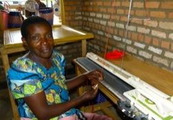 Eine afrikanische Frau sitzt an einer Strickmaschine