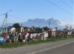Vor dem Backdrop des Tafelberges sieht man eine Stadt aus Hütten