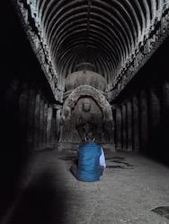 Ein Buddhist betet vor einer BuddhaStatue in einer Höhle