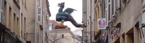 Ein Drache - das Wappentier der Stadt Metz - hängt als riesige Plastik an einem Seil über einer Einkaufsstraße in der Altstadt