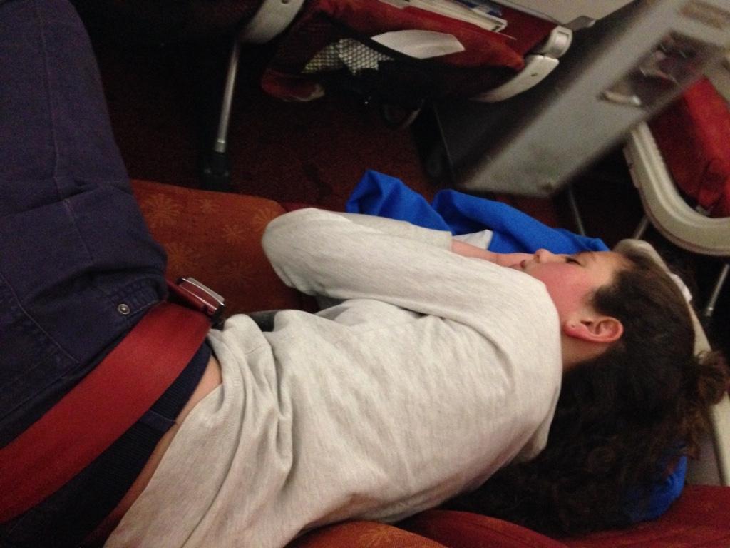 Tamuna beim Schlafen im Flugzeug, das leer genug war für einen Dreiersitz als Bett