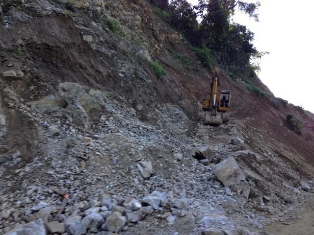 Ein Bagger gräbt einen Hügel ab, um die Straße in Nordostindien zu erweitern.