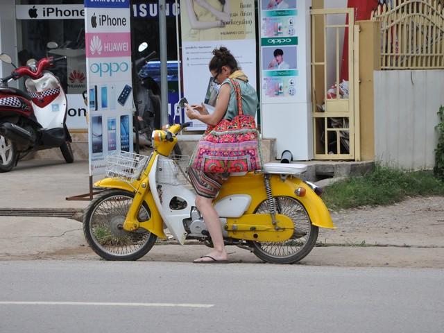 Frau auf Roller tippt auf ihrem Handy - Laos 2017